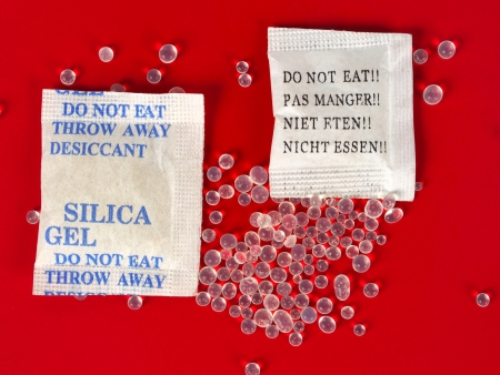 Macro of silica gel bags on red