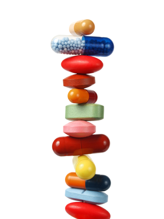 Stack of pills and capsules isolated on white background