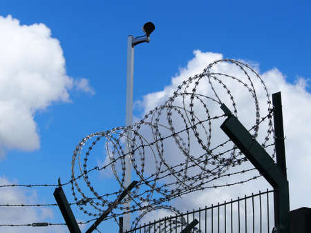 prison fence: Restricted area - fence with barbed wire and camera