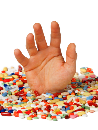 Drug addiction concept: hand reaching up from pills