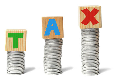 vat: Coins stacks and wooden blocks with letters forming TAX word.