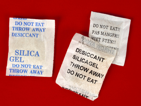 absorber: Macro of silica gel bags on red background Stock Photo