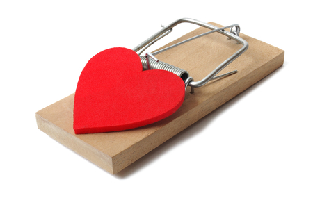 love affair: Red heart and mousetrap isolated on white background