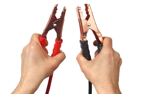 Hands with jumper cables isolated on white background Фото со стока