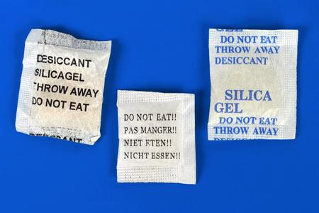 silica: Macro di sacchetti di gel di silice su sfondo blu