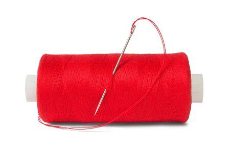 hilo rojo: Hilo de coser y aguja sobre el fondo blanco