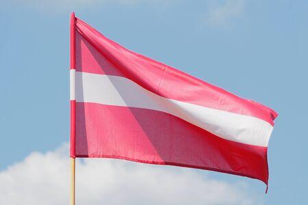 weaving: Flag of Latvia weaving against blue sky Stock Photo