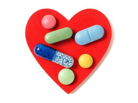forme et sante: Macro de pilules et de capsules sur le coeur rouge Banque d'images