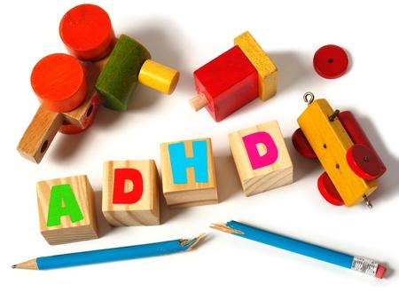 Gebroken speelgoed en houten blokken met letters ADHD