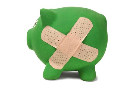 Piggy bank with bandage cross isolated on white