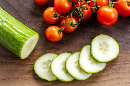 Sliced cucumber and cherry tomatoes on a butcher block. High quality photo.