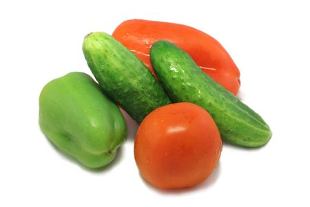 Fresh vegetables: two pepper, tomato and two cucumber lying on a white plate