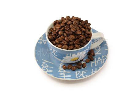 blue white cup on a saucer with the coffee beans