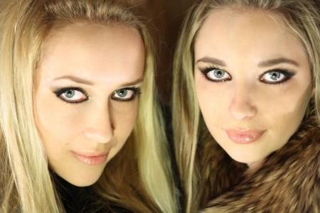 two beautiful girl brunette and blond with long hair in winter coat photo