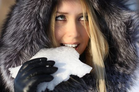 face beauty girl with blonde hair outdoors, in a fur coat, eats snow
