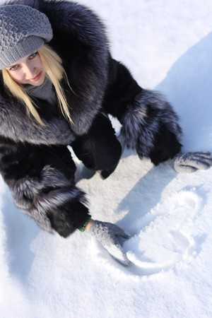 beauty girl with blonde hair outdoors draws a heart in the snow photo