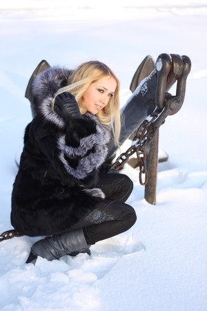 blue collar: beauty girl with blonde hair outdoors, in a fur coat near the sea anchor