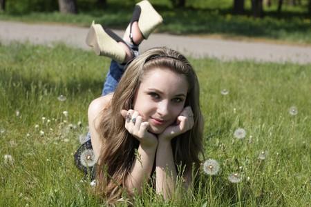 Young women lying on green grass in dandelions