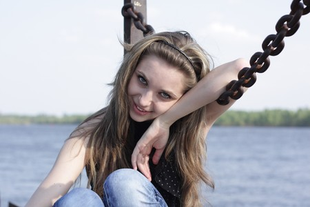 Pretty Lovely brunette girl  sits leaning on a chain Stock Photo