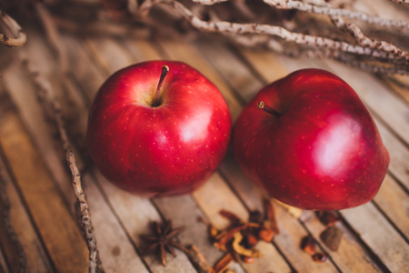 Fresh red two couple apple on brown rustic board with spices, concept. Stock Photo