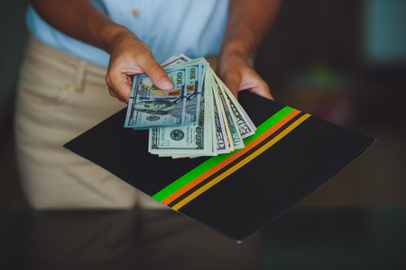 Money in human hands, women giving 100 dollars, with business folders , on a black