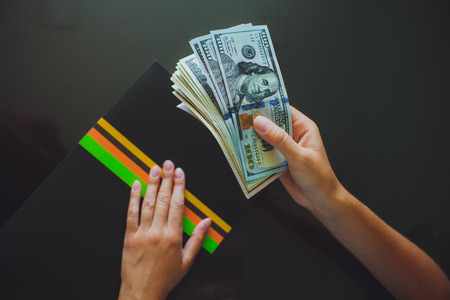 Money in human hands, women giving a lot of 100 dollars, with business folders , on a black