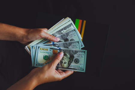 Money in human hands, women counting a lot of 100 dollars, with business folders , on a black
