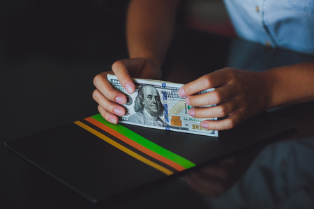 Money in human hands, women counting a lot of 100 dollars, with business folders , on a black background Stock Photo