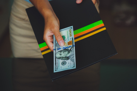 Money in human hands, women giving 100 dollars, with business folders , on a black background