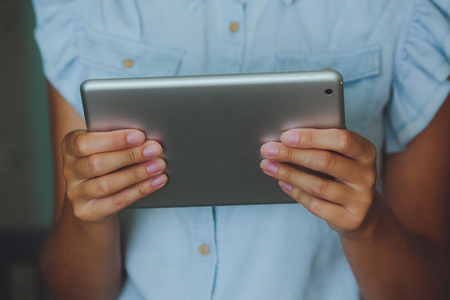 Businesswoman uses digital tablet. The tablet has a gray case and a glass screen. The woman in blue shirt.