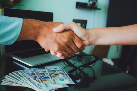 People at work: man and woman hand shaking at a meeting. Closeup shot of a two businesspeople shaking hands, glasses , money, laptop on background. Stock Photo