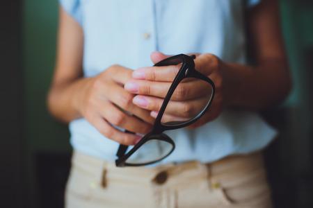 studious: Human hands woman holding retro style eyeglasses