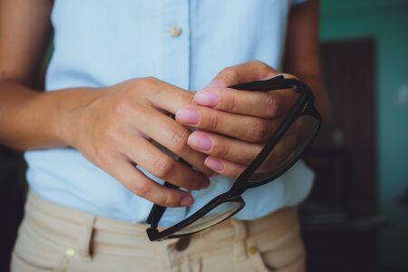 Human hands woman holding retro style eyeglasses