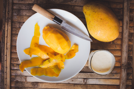 freshness fruit mango  lying on a white plate with knife. Fresh shake with milk and straw on brown board rustic