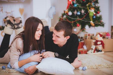 couple man and woman hugging, lie near the Christmas tree