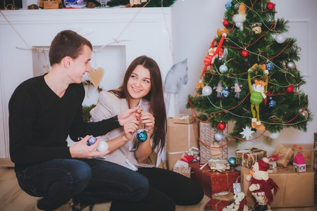 man and woman celebrating Christmas and decorating a Christmas tree with toys