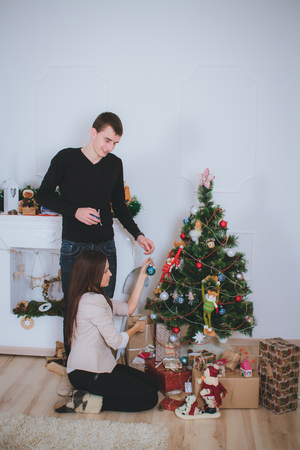 decorating christmas tree: man and woman celebrating Christmas and decorating a Christmas tree with toys