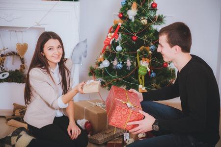 man gives a beautiful girl a Christmas present near Christmas tree