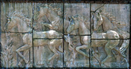 low cut: Low relief sculpture of horse.Horses in low relief statue cut out as jig saw image and water fall in front of.