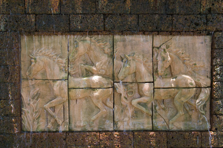 Low relief sculpture of horse.Horses in low relief statue cut out as jig saw image and water fall in front of. photo