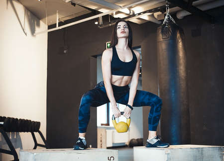Young attractive brunette girl sit ups on wooden boxes for crosstraining with weight. Female successfully practices workout and crossfit training. Blurred background and focus on young woman face view.
