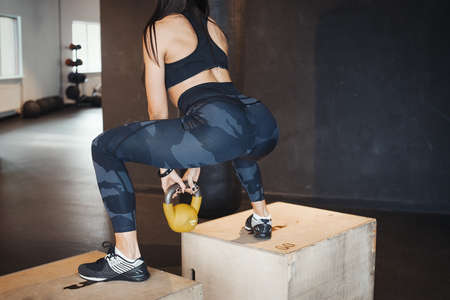 Young attractive brunette girl sit ups on wooden boxes for crosstraining with weight. Female successfully practices workout and crossfit training. Blurred background and focus on young woman back view.