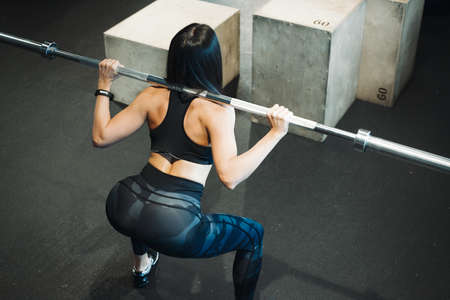 Young attractive brunette girl sit ups with barbell. Female successfully practices workout and crossfit training. Blurred background and focus on young woman back and up view. Female standing next to wooden boxes for crosstraining