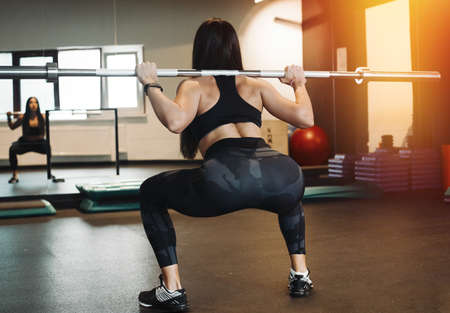Young attractive brunette girl sit ups with barbell. Female successfully practices workout and crossfit training. Blurred background and focus on young woman back and up view. Female practicing sit ups and looking in the mirror Imagens