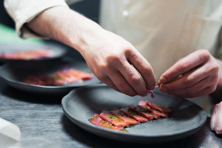 Restaurant Chef cook preparing tuna striped filet and crambling salad on the fish.