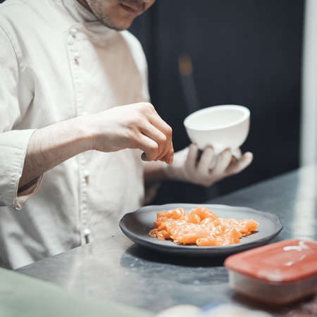 Restaurant Chef cook preparing salmon filet and crambling salad on the fish.