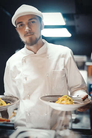 Restaurant Chef cook holding dish with pasta. Stock Photo