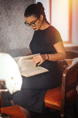 Young attractive brunette girl with glasses and black lipstick reading book on the chair.