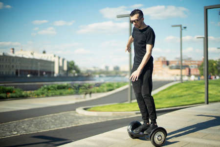 Young brunette man rides a gyroscope at park. Man is on focus, background is blurred. 版權商用圖片