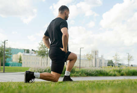 Young attractive man doing lunge outdoor in the park.